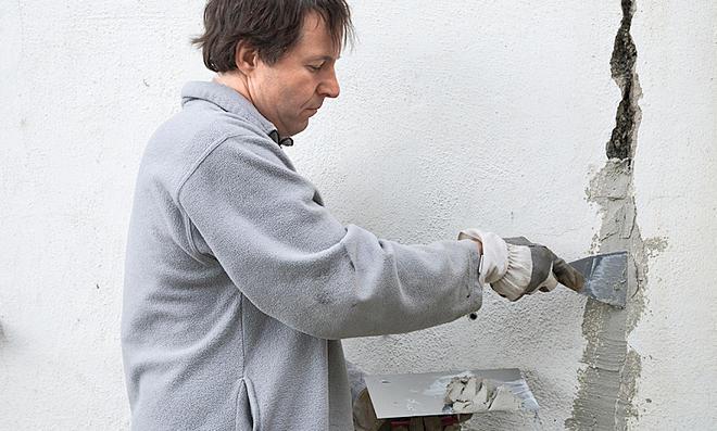 Muž opravuje prasklinu ve zdi